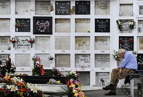 Un hombre reza a un familiar muerto en un cementerio de El Salvador. | Reuters
