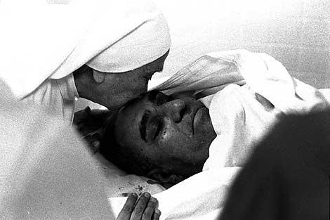 Una monja besa el cadaver del Arzobispo Oscar Arnulfo Romero cuando fue asesinado.   Ap