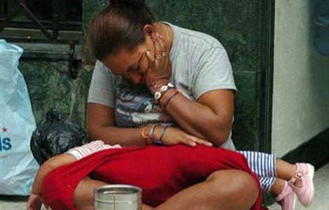 Una ciudadana hondureña pide limosnas con su hijo en Tegucigalpa. | Efe