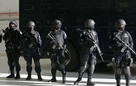 Policías custodian el vehículo que transporta a 13 presuntos miembros del cártel de Tijuana, | Efe
