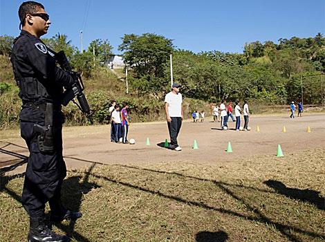 Un guardia custodia la visita de Bielsa al barrio La Campanera (El Salvador).| RV
