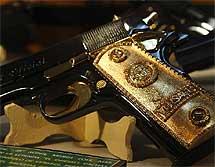 Pistola calibre 0.38 Súper con cachas doradas y el símbolo de Versace. | Efe