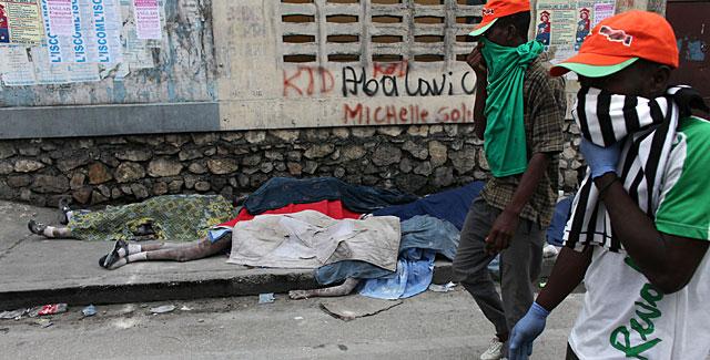 Dos hombres caminan junto a dos cuerpos en Puerto Príncipe. | AFP