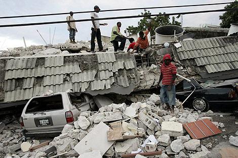 Varios hombres buscan entre los escombros de una casa. | Efe