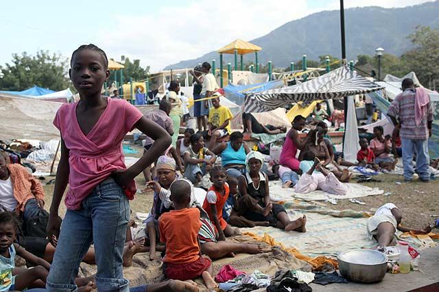 Una niña posa en una de las zonas donde se hacinan los damnificados del terremoto.   Afp