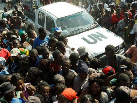 Un coche de Naciones Unidas se hace paso entre la gente que espera recibir comida. | Ap