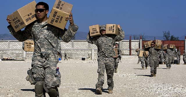 Los marines de EEUU reparten la ayuda entre la población de Haití.   Afp