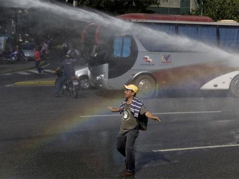 Un manifestante en Caracas se enfrenta a un cañón del água de la policía. | Reuters