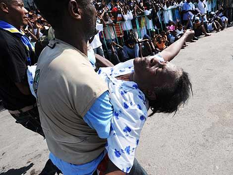 Una mujer sufre un desmayo en una de las ceremonias. | Afp