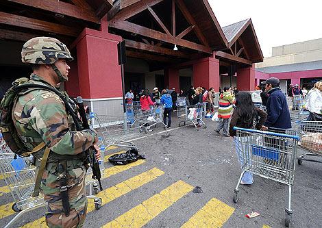 Un soldado vigila a la puerta de un supermercado. | AFP