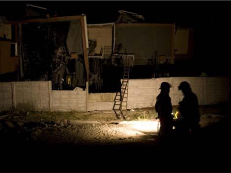 Bomberos buscando supervivientes en la noche del primer toque de queda. |Efe