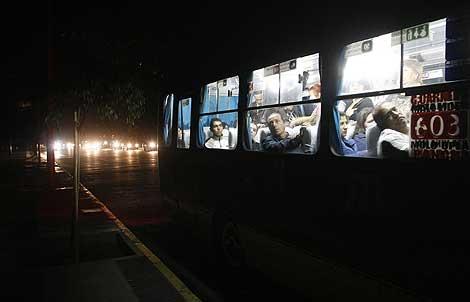 Pasajeros de un autobús observan las calles apagadas de Viña del Mar.   Reuters