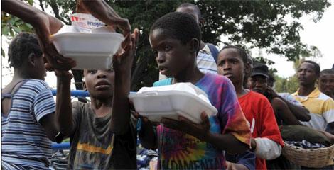 Niños haitianos reciben comida. | Efe