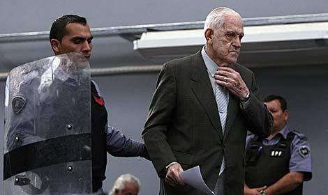Reynaldo Bignone, escoltado por un policía. | Reuters