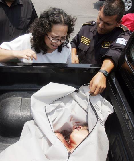 Un policía muestra a una mujer el cadáver de una joven asesinada en la localidad guatemalteca de San Pedro Ayampuc. | AFP