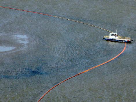 Un barco intenta controlar el avance de la mancha de crudo. | Efe