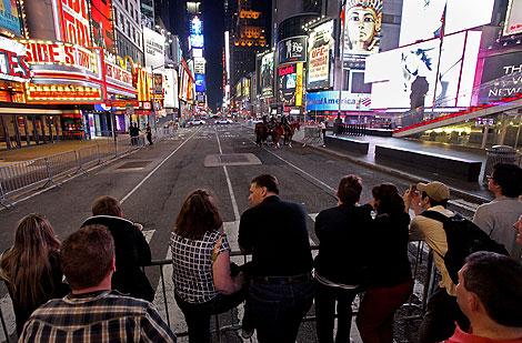 Los peatones evacaudos de Times Square observan la plaza desierta. | Ap