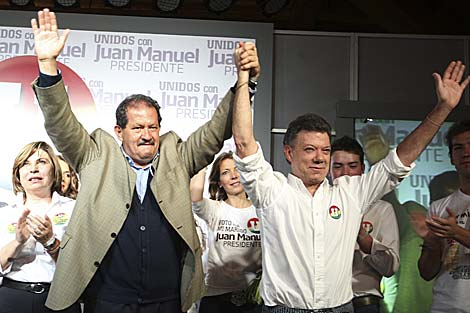 Santos (d) y Angelino Garzón celebran los resultados de la primera vuelta.   Reuters