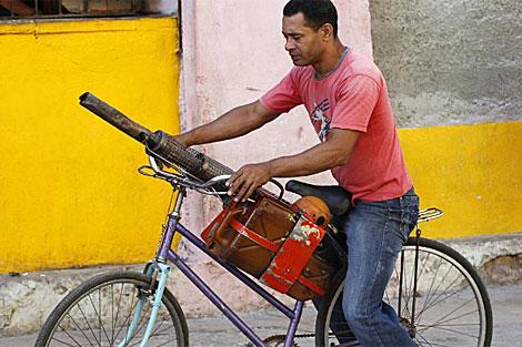 Un fumigador en su bicicleta y aparato de fumigación en La Habana.