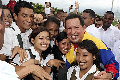 Chávez abraza a varios niños antes de encontrarse con Santos. | Reuters
