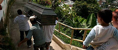 Varios pandilleros trasladan a uno de sus compañeros muerto. | EFE