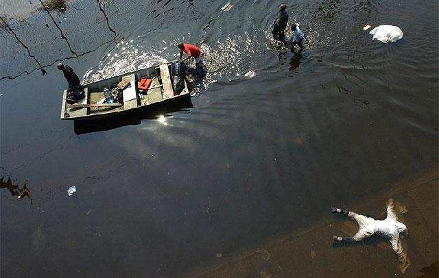 Una víctima de las inundaciones tras el huracán junto a una lancha de rescate. | Ap