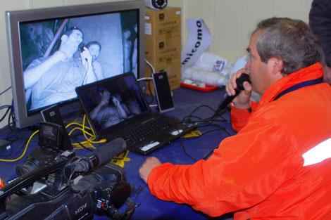 El director del equipo de rescate habla con uno de los mineros. | Reuters