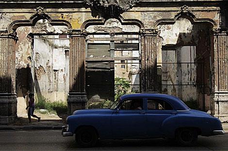 Un coche pasa por un edificio derrruido de La Habana. | Reuters