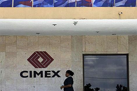 Una mujer pasa frente a la sede de CIMEX en La Habana. | Reuters