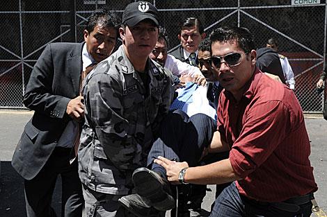 El presidente Correa es transportado por sus guardaespaldas tras el ataque. | Efe