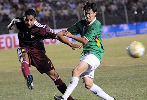 El boliviano Joselito Vaca (d) disputa el balón con el venezolano Grenddy Perozo (i). | Efe
