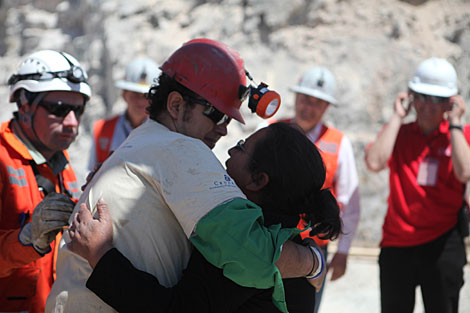 El minero Daniel Herrera abraza a su esposa tras salir de a la superficie. | Reuters