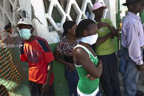 Algunos vecinos de St. Marc, norte, se protegen con máscaras.   Reuters