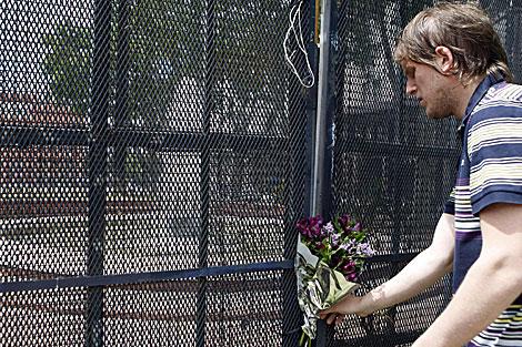 Un joven coloca flores frente a la Casa Rosada. | Efe