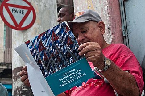 Un cubano lee el proyecto de reformas económicas. | AFP