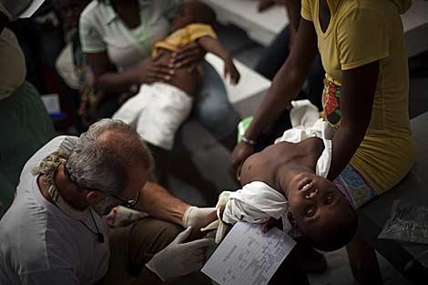 Un niño con síntomas de cólera es atendido por un médico en Puerto Príncipe. | AP