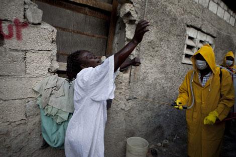 La madre de Stephanie, una joven de 16 años que murió por cólera, llora ante la llegada de los trabajadores que recogen cadáveres. I Efe