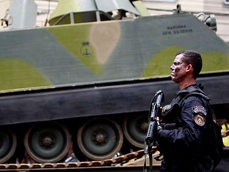 Un agente de la policía militar, ante un tanque en Vila Cruzeiro. | AP
