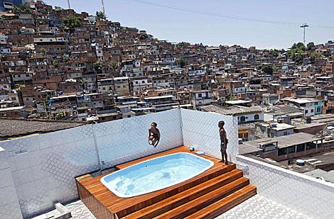 Dos niños se bañan en la piscina de 'Pezão' tras la invasión. | AFP