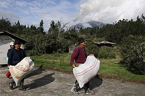 Un grupo de campesinos evacua de la posible zona de desastre. | AFP