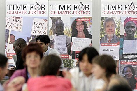 Varias personas charlan en Cancún con carteles detrás sobre el cambio climático. | Reuters