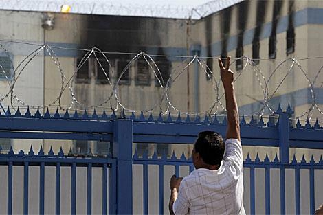 Un familiar hace gestos frente a la cárcel de San Miguel. | Reuters