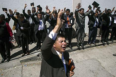 Integrantes de la Iglesia Evangélica oran en frente al penal de San Miguel. | Efe