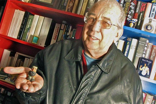 El escritor Norberto Fuentes en la biblioteca de su penthouse en Miami con una estatuilla de Castro en su mano. | Rui Ferreira