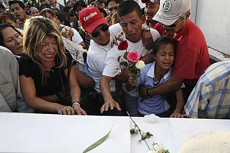 Una familia llora la muerte de dos niñas de 8 y 12 años durante un tiroteo en Guadalajara.   Efe