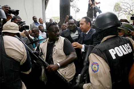 Duvalier (centro) es conducido a la Fiscalía bajo arresto. | AFP