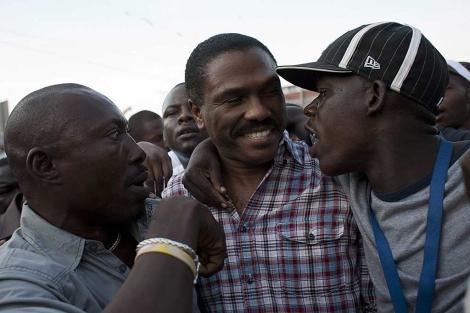 El candidato presidencial Jude Celestin (c), abrazado por admiradores. | Efe