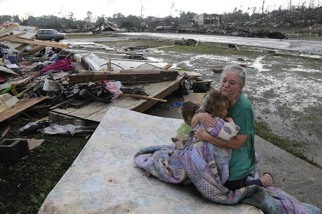 Una mujer abraza a su nieta sobre un colchón tirado entre escombros. | AP