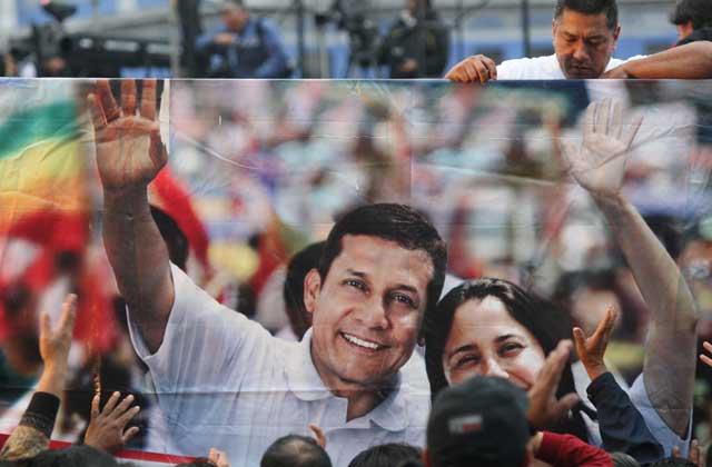 Un simpatizante de Humala sostiene un cartel con la imagen del candidato y su esposa, Nadine Heredia.   Efe