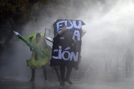 Estudiantes chilenos disfrazados durante la manifestación, enfrentan a la Policía. | Efe